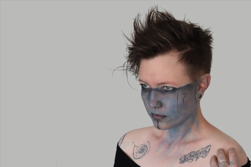 Robyn Ferguson is a musician from South Africa with blue war paint and tattoos on her face for her EP Harbinger.