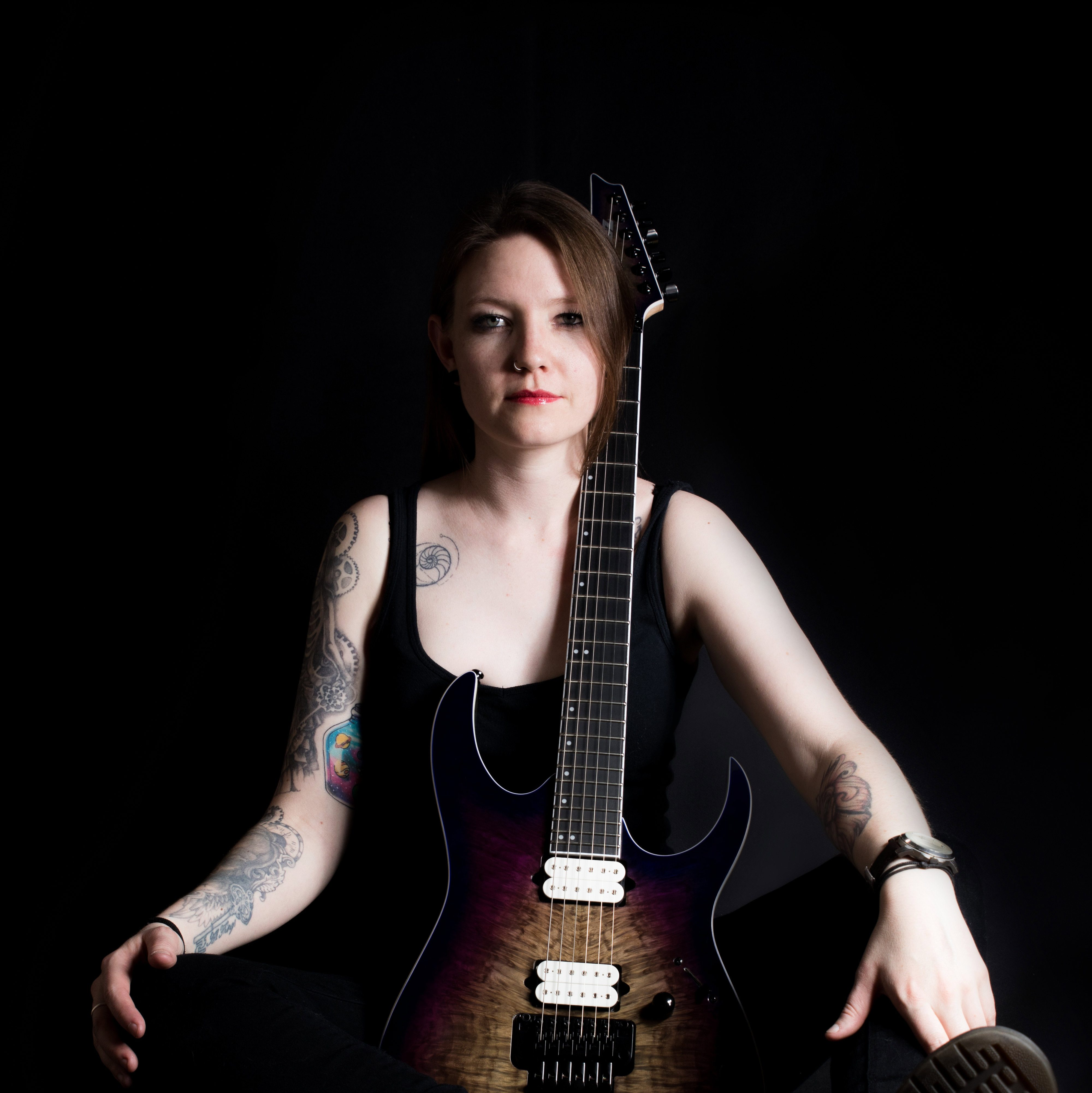 Robyn Ferguson from South Africa sitting with her Ibanez guitar. Robyn has many tattoos.