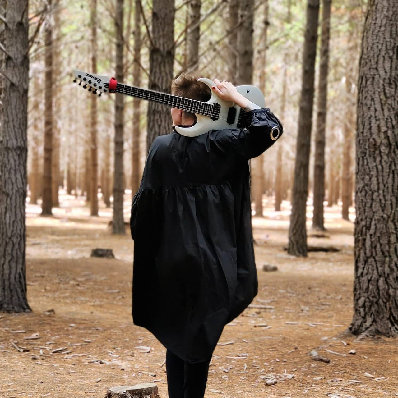 Robyn Ferguson, a musician from South Africa, is holding her Ibanez guitar behind her head while walking through the forest in Cape Town.